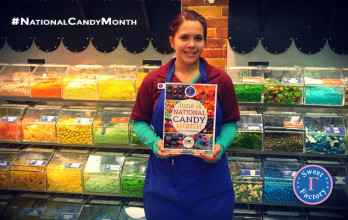 A Sweet Factory Associate Displays Custom In Store Signage Created By NCA To Help The Candy Retailer Celebrate #NationalCandyMonth.